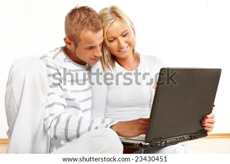 Portrait of a happy couple sitting on the floor with laptop