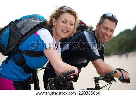Portrait of a happy couple smiling with their bikes outdoors - stock photo