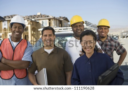 Portrait of a happy couple with a group of architects at construction site - stock photo