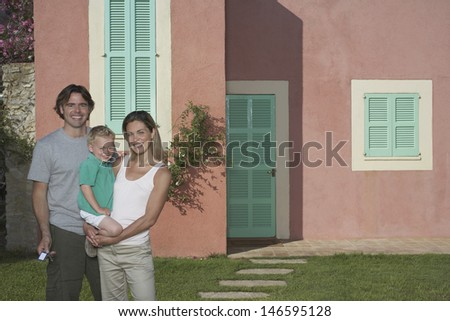 Portrait of a happy couple with boy in front of house - stock photo
