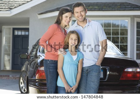 Portrait of a happy couple with daughter standing against car and house - stock photo