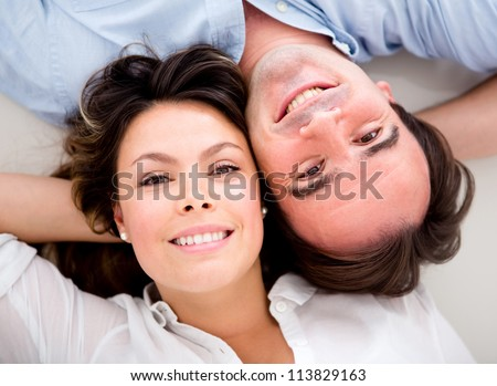 Portrait of a happy couple with heads together on the floor
