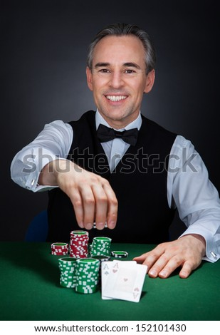 Portrait of a happy croupier holding gambling chips on table - stock photo