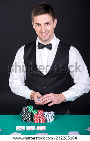 Portrait of a happy croupier is holding playing cards, gambling chips on table. - stock photo
