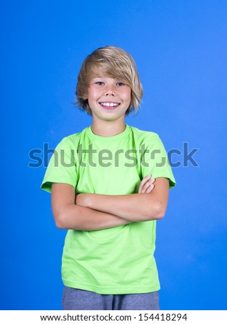 Portrait of a happy cute boy in green t-shirt on a blue background. - stock photo