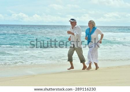 Portrait of a happy elderly couple running  on beach - stock photo