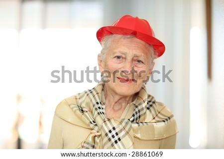 Portrait of a happy elderly woman in red hat. Shallow DOF. - stock photo