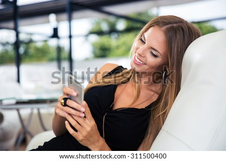 Portrait of a happy elegant woman in black dress using smartphone