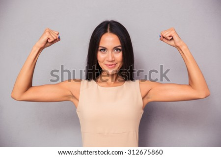 Portrait of a happy elegant woman showing her biceps on gray background - stock photo