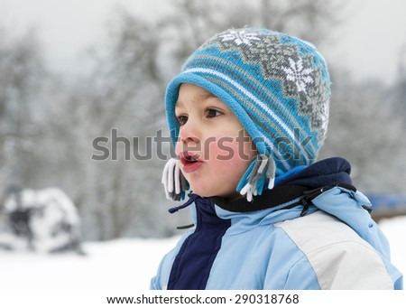 Portrait of a happy excited child in winter park, profile view. - stock photo