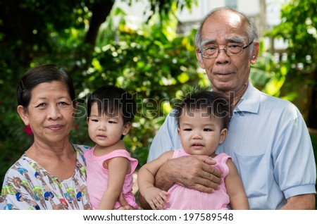 Portrait of a happy extended asian family at the park - stock photo