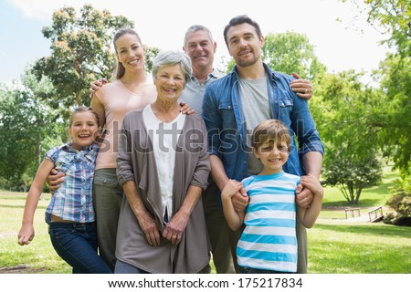 Portrait of a happy extended family standing at the park - stock photo