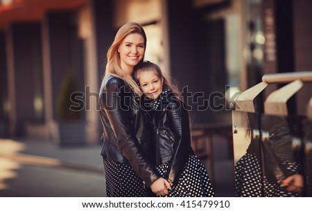 portrait of a happy family: a young beautiful woman with her little cute daughter. Young daughter hugs mother in autumn city outdoor - stock photo