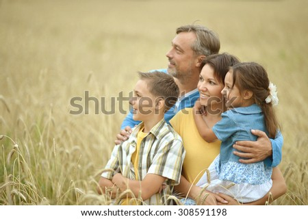 Portrait of a happy family at summer rye field - stock photo