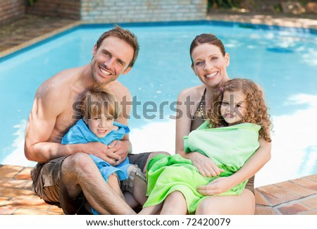 Portrait of a happy family beside the swimming pool - stock photo