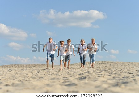 Portrait of a happy family doing exercises on the sand in the summer