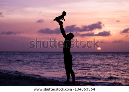 Portrait of a happy family - father with baby having fun on the beach at sunset in the Caribbean part of Mexico, Riviera Maya. - stock photo