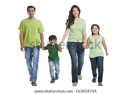 Portrait of a happy family holding hands and walking - stock photo