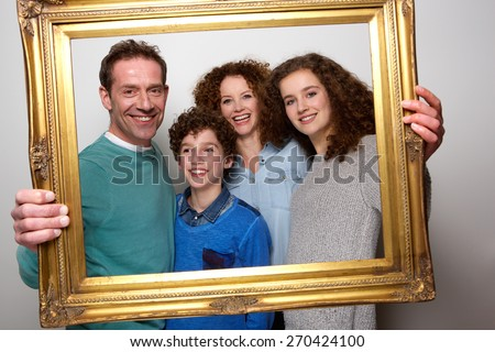 Portrait of a happy family holding picture frame and smiling - stock photo