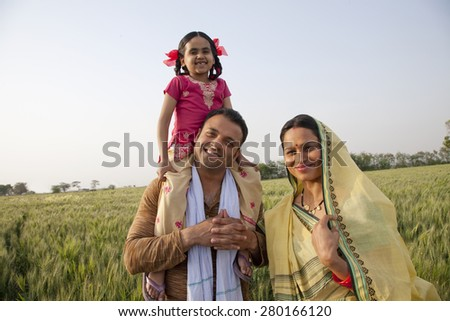 Portrait of a happy family in field with girl on father's shoulders - stock photo
