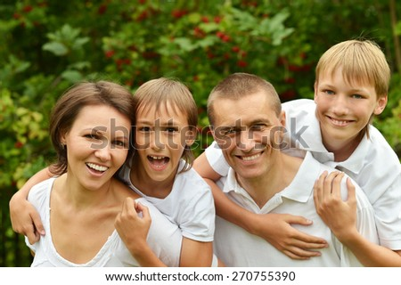 Portrait of a happy family in summer park - stock photo