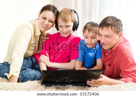 portrait of a happy family lying on the carpet with a laptop