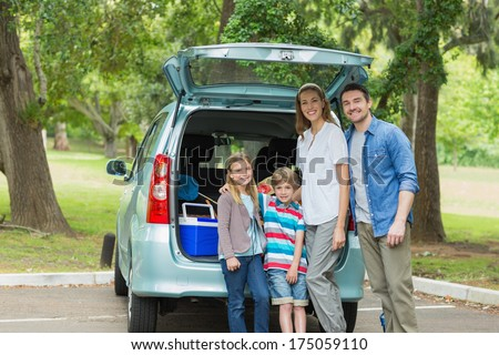 Portrait of a happy family of four by car trunk while on picnic - stock photo