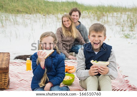 Portrait of a happy family of four enjoying picnic at the beach - stock photo