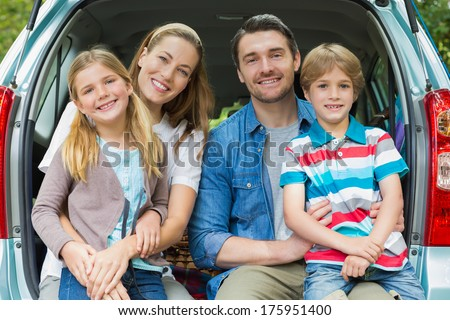 Portrait of a happy family of four sitting in car trunk while on picnic