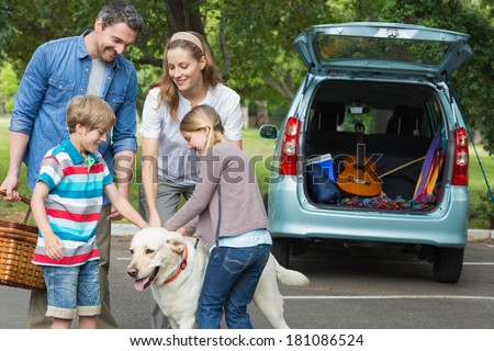 Portrait of a happy family of four with pet dog at picnic - stock photo