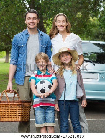 Portrait of a happy family of four with picnic basket