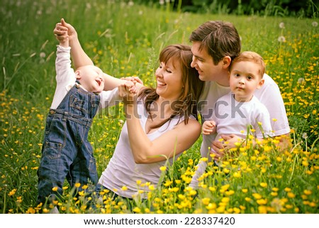 Portrait of a happy family on the meadow - stock photo