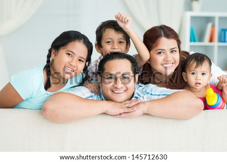 Portrait of a happy family posing at camera together - stock photo