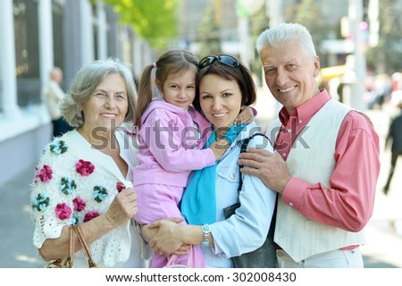 Portrait of a happy family relaxing at city - stock photo