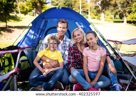 Portrait of a happy family sitting in front of a tent