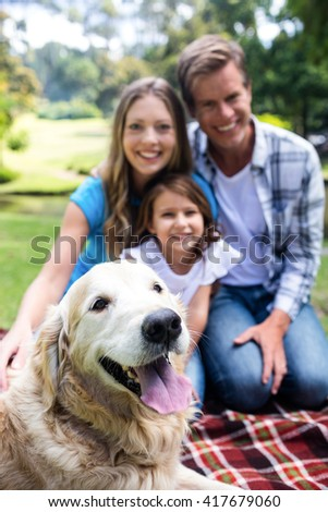 Portrait of a happy family sitting in the park with their dog - stock photo