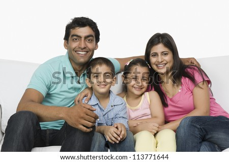 Portrait of a happy family sitting on a couch - stock photo