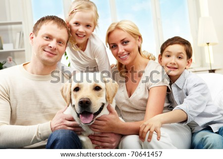 Portrait of a happy family sitting on sofa with a dog, looking at camera and smiling - stock photo