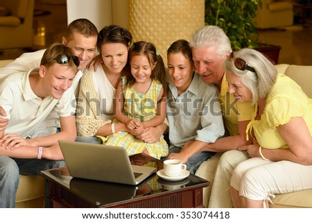 Portrait of a happy family sitting with laptop - stock photo