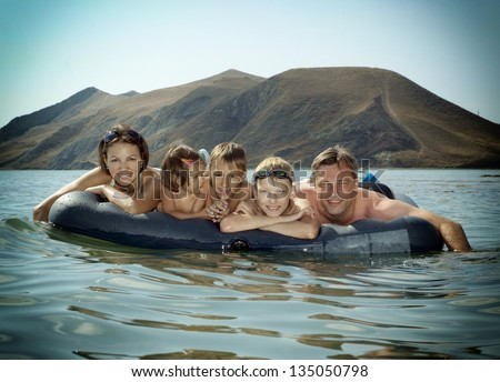 portrait of a happy family swimming on an air mattress - stock photo