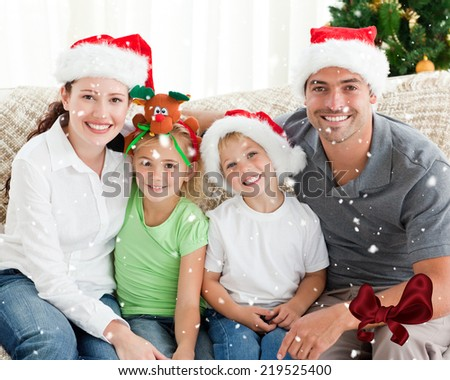 Portrait of a happy family with Christmas hats sitting on the sofa against digitally generated red shiny bow - stock photo