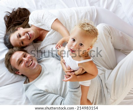 Portrait of a happy family with cute little girl playing in bed - stock photo