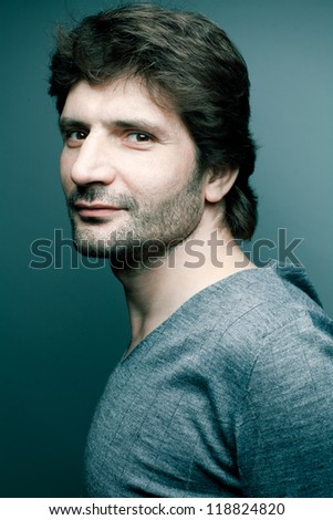 Portrait of a happy fashionable handsome man in gray sweater (pullover) over dark blue (green) background with a friendly smile. Close-up. Studio shot - stock photo