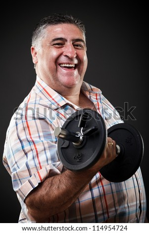 Portrait of a happy fat man with dumbbell on gray background - stock photo