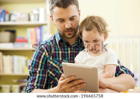Portrait of a happy father and his little daughter using digital tablet at home - stock photo