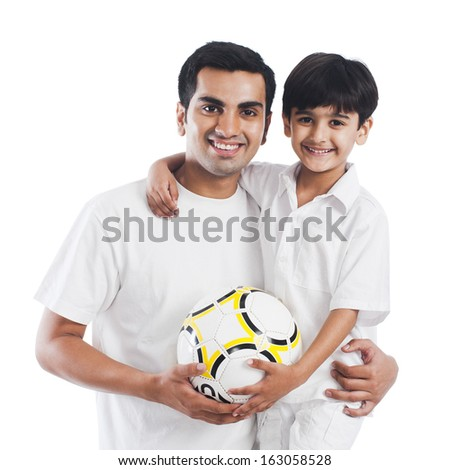 Portrait of a happy father and son with football - stock photo