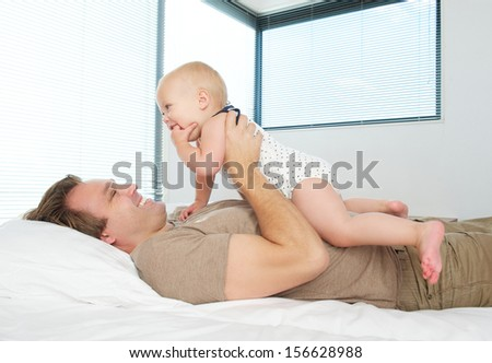 Portrait of a happy father holding baby in bed