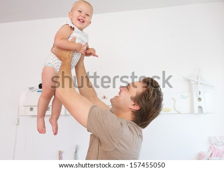 Portrait of a happy father playing with cute baby at home - stock photo
