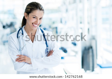 Portrait of a happy female doctor at the gym - stock photo