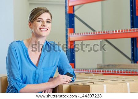 Portrait of a happy female employee smiling in warehouse - stock photo